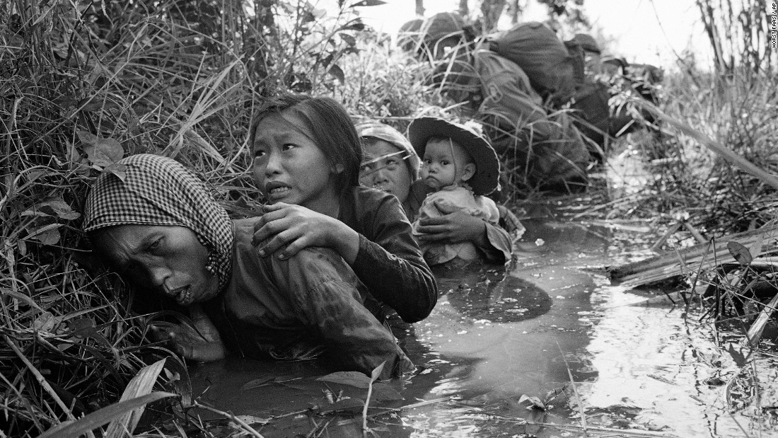 Women and children crouch in a muddy canal as they take cover from intense Viet Cong fire at Bao Trai, about 20 miles west of Saigon, in January 1966.