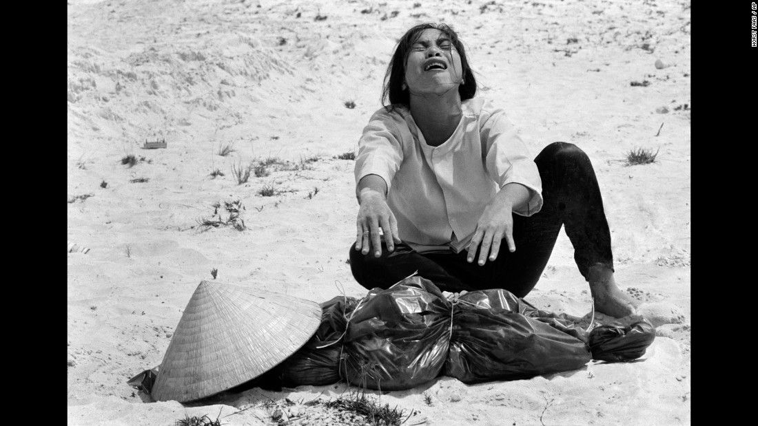 A South Vietnamese woman mourns over the body of her husband, which was found with 47 others in a mass grave near Hue in April 1969.