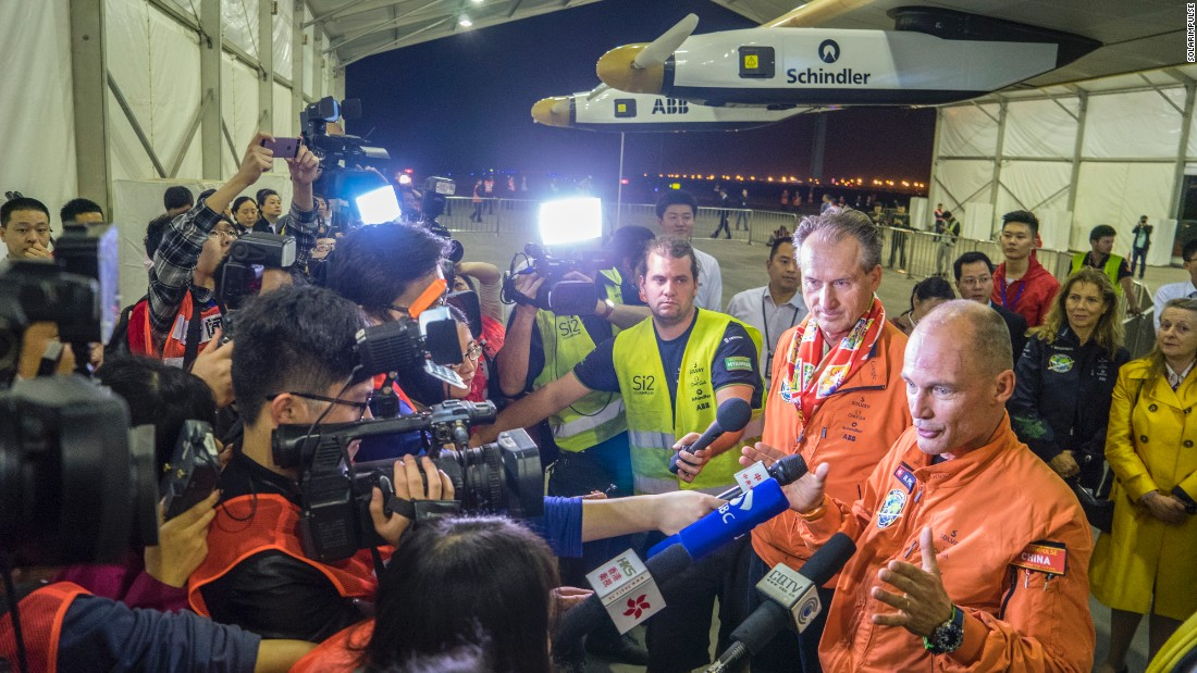 Borschberg and Piccard are welcomed by a crowd of reporters after landing in Chongqing.