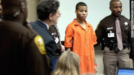 VIRGINIA BEACH:  Lee Boyd Malvo (C) is escorted by deputies as he is brought into court to be identified by a witness during the murder trial for sniper suspect John Allen Muhammad at the Virginia Beach Circuit Court 22 October, 2003, in Virginia Beach, Virginia. (DAVIS TURNER/AFP/Getty Images)