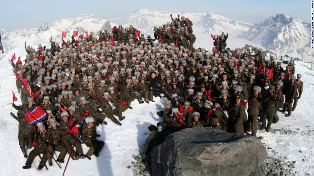 Kim Jong Un, center, poses with soldiers on the snow-covered top of Mount Paektu in an April 18 photo released by South Korean news agency Yonhap.