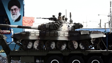 A soldier sits atop a T-72 tank as it rolls past a portrait of Ayatollah Ali Khamenei April 18.