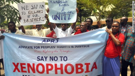Demonstrators hold banners during a rally called by the NGO Advocate for Peoples' Rights and Justice in front of the office of the South African television DSTV, on April 20, 2015 in Abuja to protest against anti-immigrant violence that erupted last week in South Africa in the economic capital Johannesburg and Durban.