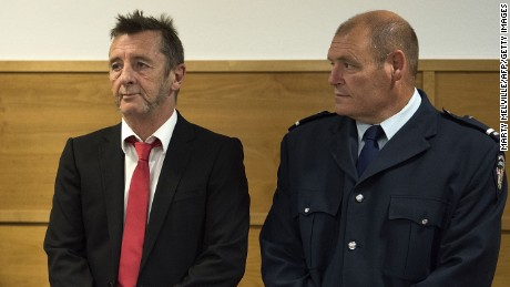 Former AD/DC drummer Phil Rudd (L) stands in the dock at the district court in Tauranga, New Zealand on April 21.