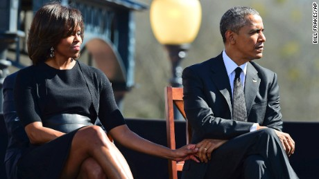 First lady Michelle Obama holds the hand of her husband during a ceremony marking 50 years since Bloody Sunday.