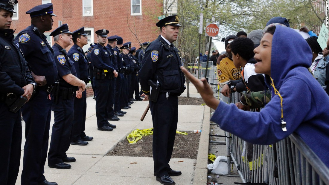 Members of the Baltimore Police Department stand guard Thursday, April 23, outside the department's Western District station during a protest.