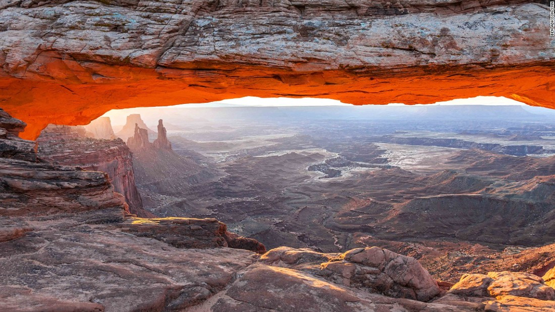 Enjoying the sunrise from Mesa Arch in the Island in the Sky district of Canyonlands National Park is a must-do park experience. Mesa Arch has been made famous in photos thanks to the early morning orange glow on its bottom and the framing it provides for Washerwoman Arch further down the canyon.