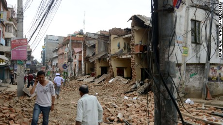 Caption:Nepalese people walk past collapsed buildings at Lalitpur, on the outskirts of Kathmandu on April 25, 2015. A powerful 7.9 magnitude earthquake struck Nepal, causing massive damage in the capital Kathmandu with strong tremors felt across neighbouring countries. AFP PHOTO / PRAKASH MATHEMA (Photo credit should read PRAKASH MATHEMA/AFP/Getty Images)