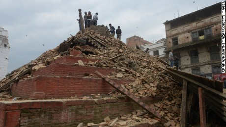 Caption:People gather in Kathmandu's Durbar Square, a UNESCO World Heritage Site that was severely damaged by an earthquake on April 25, 2015. A massive 7.8 magnitude earthquake killed hundreds of people April 25 as it ripped through large parts of Nepal, toppling office blocks and towers in Kathmandu and triggering a deadly avalanche that hit Everest base camp. AFP PHOTO / PRAKASH MATHEMA (Photo credit should read PRAKASH MATHEMA/AFP/Getty Images)