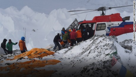 An injured person is loaded onto a rescue helicopter at Everest Base Camp on April 26, 2015, a day after an avalanche triggered by an earthquake devastated the camp. Rescuers in Nepal are searching frantically for survivors of a huge quake on April 25, that killed nearly 2,000, digging through rubble in the devastated capital Kathmandu and airlifting victims of an avalanche at Everest base Camp. The bodies of those who perished lie under orange tents. AFP PHOTO/ROBERTO SCHMIDT (Photo credit should read ROBERTO SCHMIDT/AFP/Getty Images)