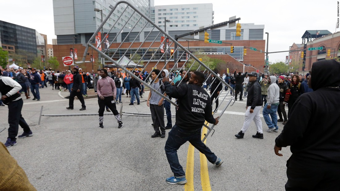 A protester throws a barricade at a bar near Oriole Park at Camden Yards after a rally on April 25.