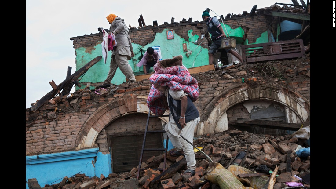 Residents rescue items from the debris of houses damaged in the quake in Kathmandu on April 27.