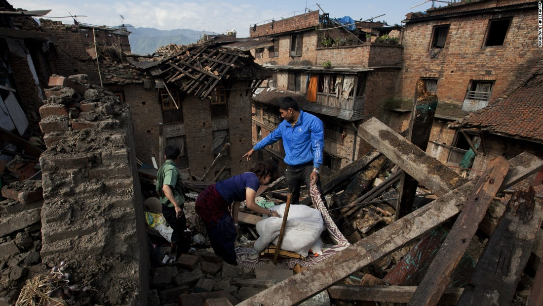 A family collects belongings from their home in Bhaktapur, Nepal, on Monday, April 27.