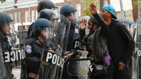 A Baltimore Police officers in riot gear push protestors back along Reisterstown Road near Mondawmin Mall, April 27, 2015 in Baltimore, Maryland.