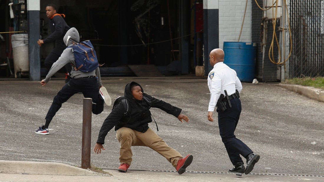 Baltimore Police Commissioner Anthony Batts chases away protesters in a parking lot on April 27.