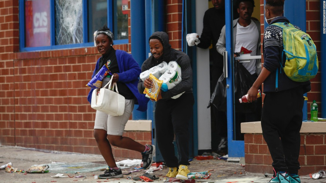 People carry goods out of a CVS pharmacy on April 27.