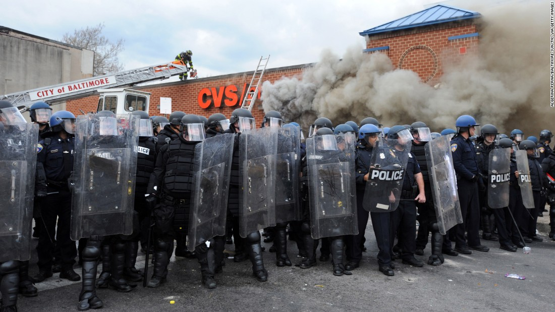Police form a barrier between protesters and a burning CVS being attended to by firefighters on April 27.