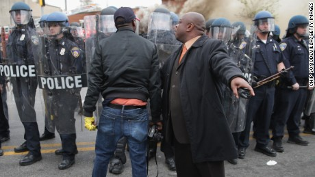 BALTIMORE, MD - APRIL 27:  A man attempts to calm a fellow demonstrator as they face off with Baltimore Police at the corner of Pennsylvania and North avenues during violent protests following the funeral of Freddie Gray April 27, 2015 in Baltimore, Maryland. Gray, 25, who was arrested for possessing a switch blade knife April 12 outside the Gilmor Homes housing project on Baltimore's west side. According to his attorney, Gray died a week later in the hospital from a severe spinal cord injury he received while in police custody.  (Photo by Chip Somodevilla/Getty Images)