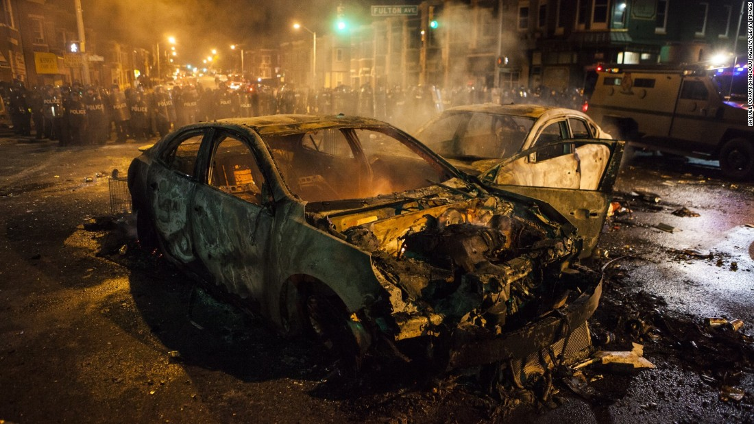 Police retreat from burned-out cars in an intersection on Monday, April 27.