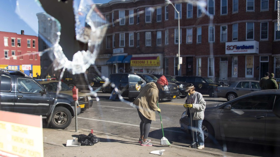 "Two women sweep up the streets in Baltimore -- reflected in the broken window of a storefront on April 28. <a href=""http://www.cnn.com/2015/04/29/us/gallery/baltimore-protests-cleanup/index.html"">See more photos of the cleanup efforts.</a>"