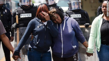 "Jerrie Mckenny, left, and her sister Tia Sexton embrace as demonstrators hold hands and sing the hymn ""Amazing Grace"" in the streets of Baltimore on Tuesday, April 28."