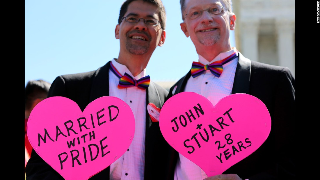 Outside the Supreme Court, John Lewis and Stuart Gaffney of San Francisco hold signs celebrating their marriage.