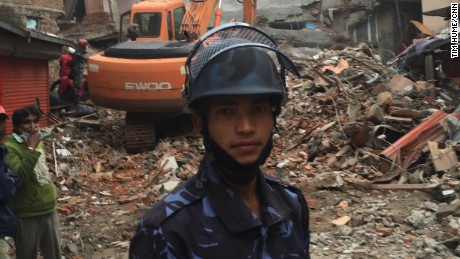 Tejush Swarnakar, Nepal police, stands in front of the rubble of a cluster of six-storey guest houses.