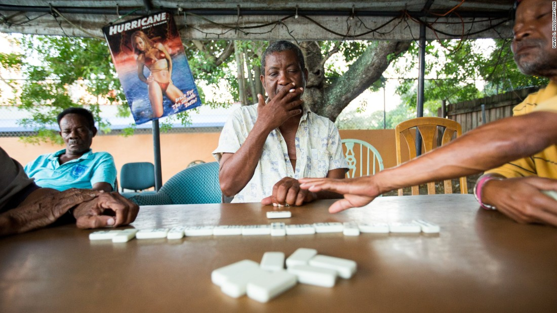 Members of Miami's enormous Afro-Caribbean community enjoy a game of dominoes outside.