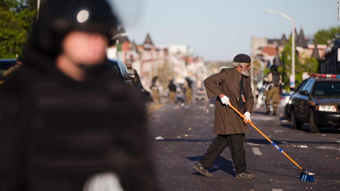 A man sweeps the street as law enforcement officers stand guard on April 28.
