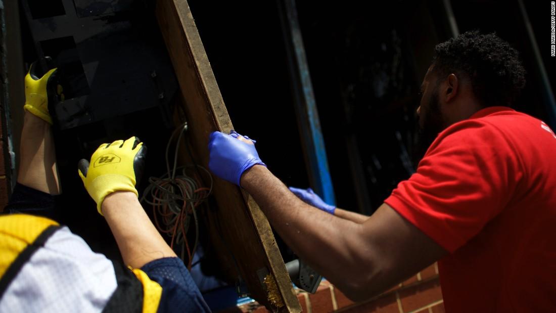Men wearing work gloves help clear debris on April 28.