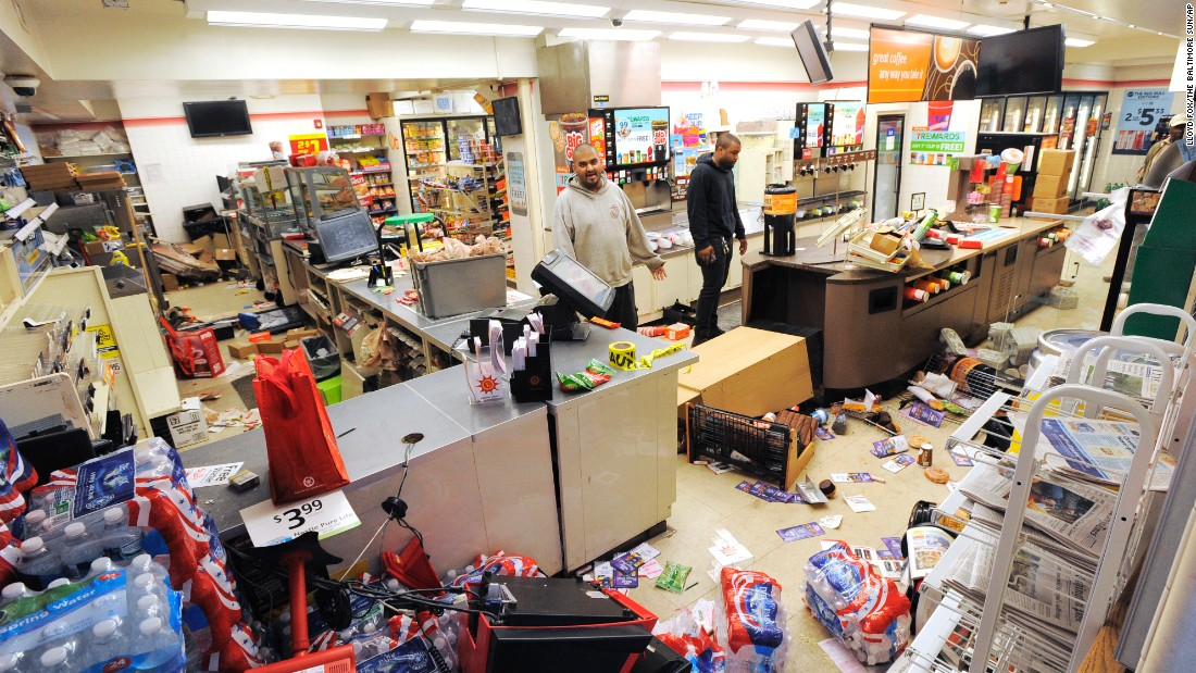 Employee Sam Wirtz, left, surveys the damage to his store that came during the unrest on Monday, April 27.