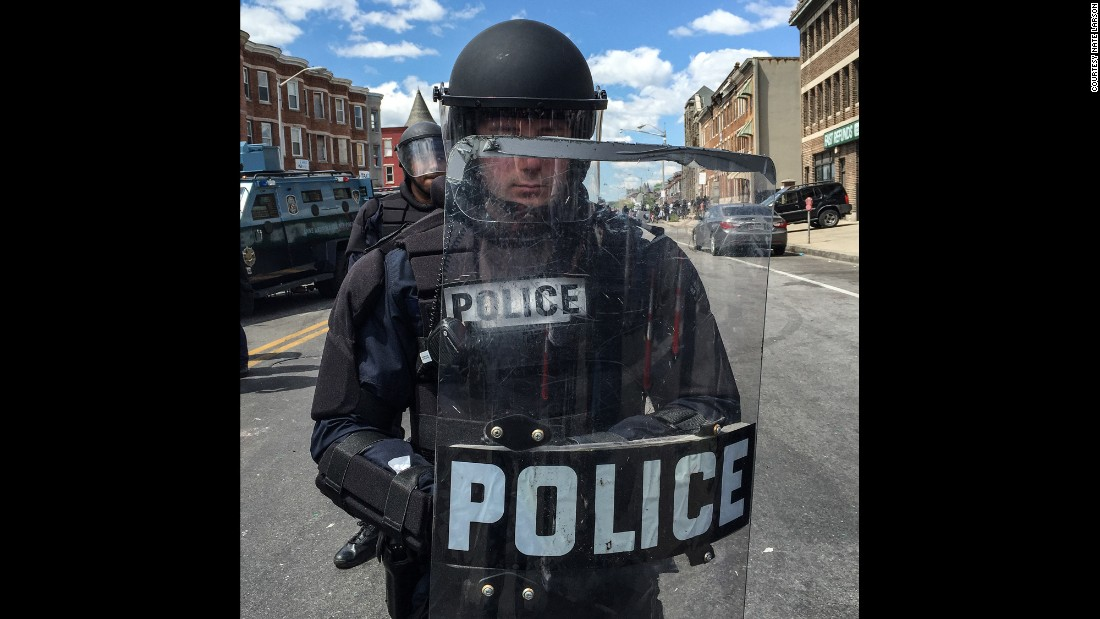 "At around noon, Larson took portraits of police officers in full riot gear, forming a line blocking North Avenue. ""We watched the police mass, from a few officers when we arrived to one hundred-plus over the span of an hour,"" he said."