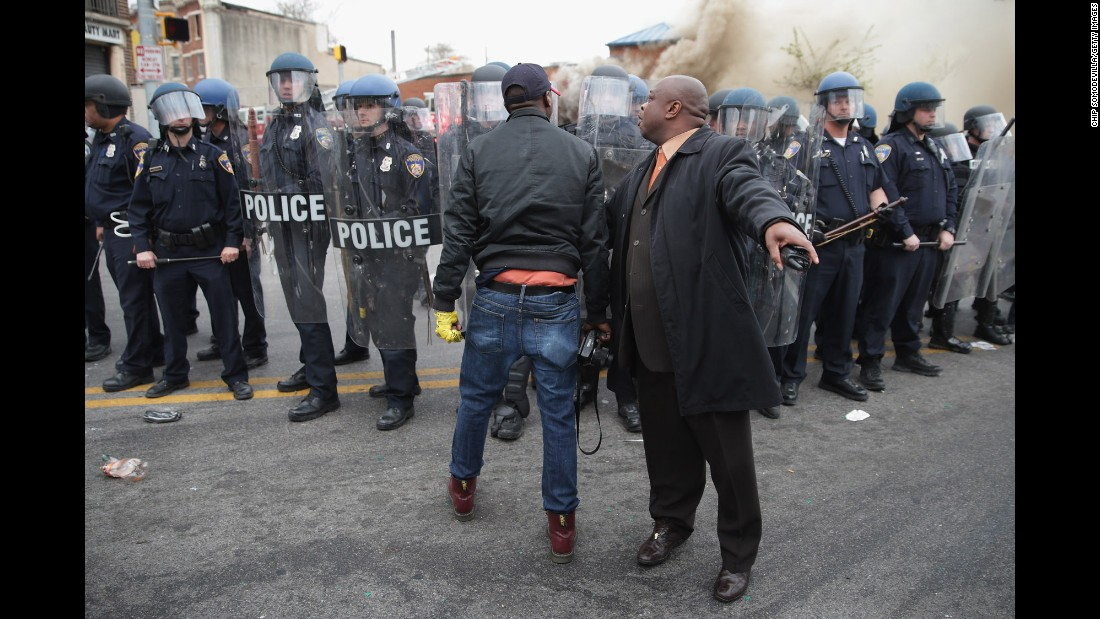 "A man attempts to calm a fellow demonstrator as they face police in Baltimore in April 2015. Riots broke out after <a href=""http://www.cnn.com/2015/04/27/us/gallery/freddie-gray-funeral/index.html"">the funeral for Freddie Gray</a>, who died of a severe spinal cord injury while in police custody. His death sparked <a href=""http://www.cnn.com/2015/04/23/us/gallery/freddie-gray-protest/index.html"">protests in Baltimore</a> and raised long-simmering tensions between police and residents."