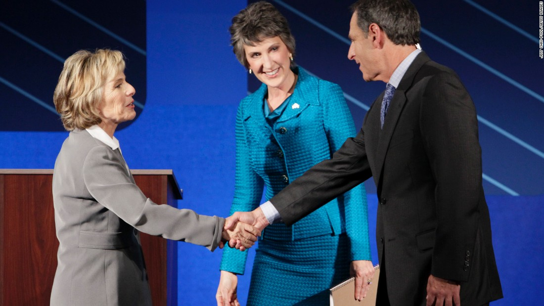 Boxer, left, and Fiorina, center, greet moderator Randy Shandobil, right, after a debate on the campus of Saint Mary's College September 1, 2010, in Moraga, California.