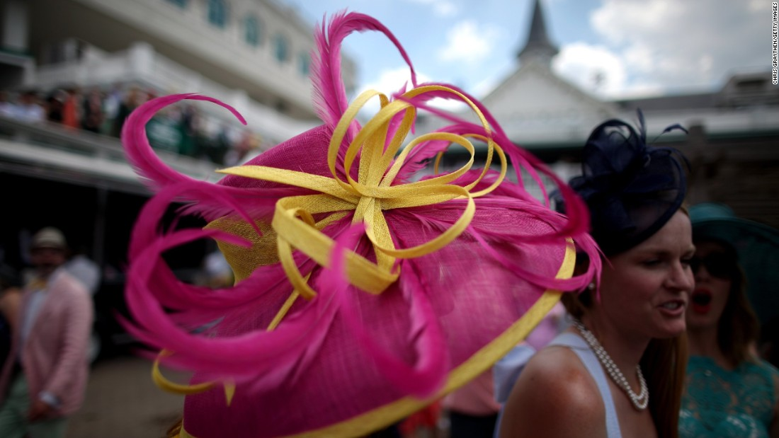 A woman wears an eye-catching pink and yellow hat prior to the Derby. Advice from the Kentucky Derby: If your hat is having a pattern party, keep the dress design simple.