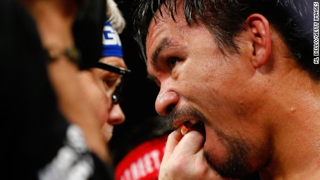 Trainer Freddie Roach adjust Manny Pacquiao's mouthguard.