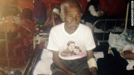 Funchu Tamang, 101, sits at a hospital in Nuwakot district on Sunday after being rescued from his collapsed home.