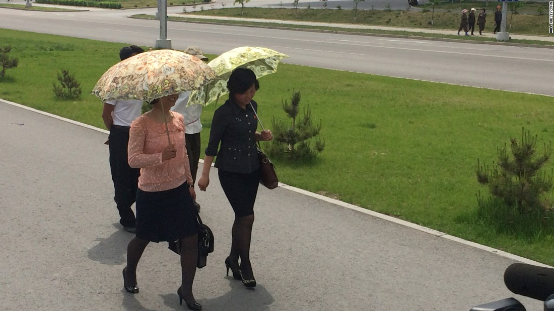 Pyongyang women wear their Sunday best, and carry ornate umbrellas to shield themselves from the sun.