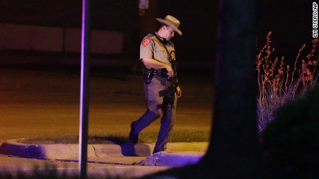 A Texas state trooper stands guard at a parking lot near the Curtis Culwell Center where a provocative contest for cartoon depictions of the Prophet Muhammad was held Sunday, May 3, 2015, in Garland, Texas. The contest was put on lockdown Sunday night and attendees were being evacuated after authorities reported a shooting outside the building. (AP Photo/LM Otero)