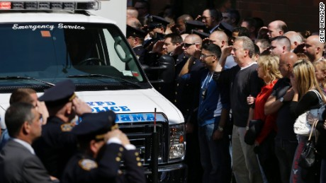 Police officers and others salute as the body of Brian Moore leaves Jamaica Hospital in New York, Monday, May 4, 2015. Brian Moore, a 25-year-old police officer shot in the head over the weekend while attempting to stop a man suspected of carrying a handgun, has died from his injuries, the third New York Police Department officer slain in the line-of-duty in five months, a City Hall official said Monday. (AP Photo/Seth Wenig)