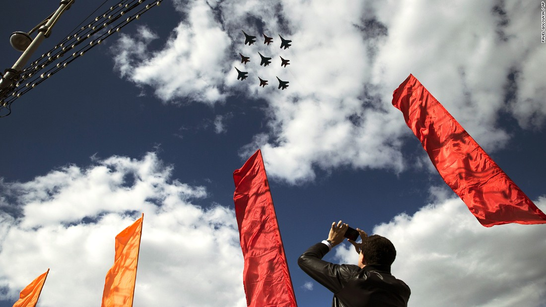A man takes a picture of Russian Air Force fighter jets on Tuesday as they fly over Moscow during a rehearsal for the Victory Day military parade.
