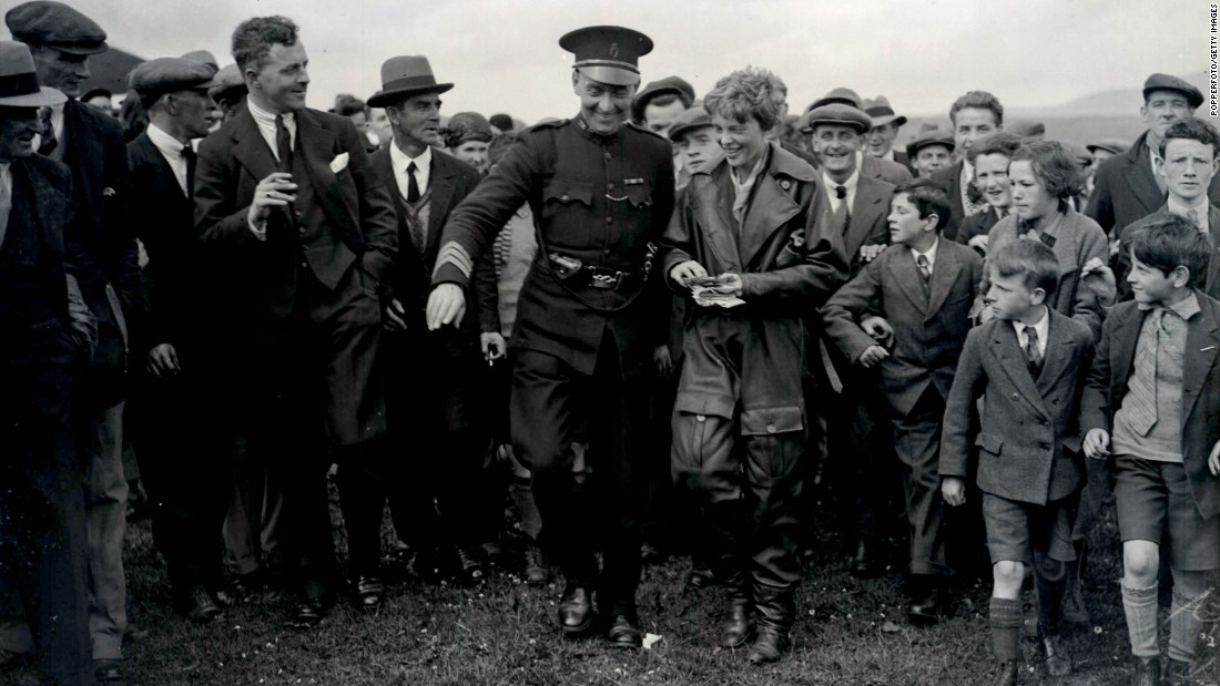 Earhart is escorted from her plane by a policeman in Londonderry, Northern Ireland, on May 23, 1932. Prior to completing the solo flight, Earhart was the first woman to fly across the Atlantic as a passenger in 1928.