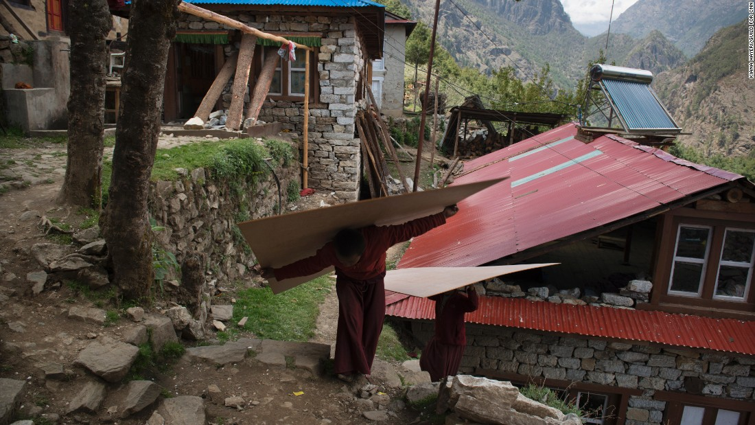 Young monks take wood up to a 500-year-old monastery that was heavily damaged in the earthquake. They are afraid that what remains might still come tumbling down.