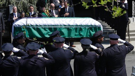 Police officers salute as the casket carrying the body of NYPD Officer Brian Moore arrives for his funeral Mass.