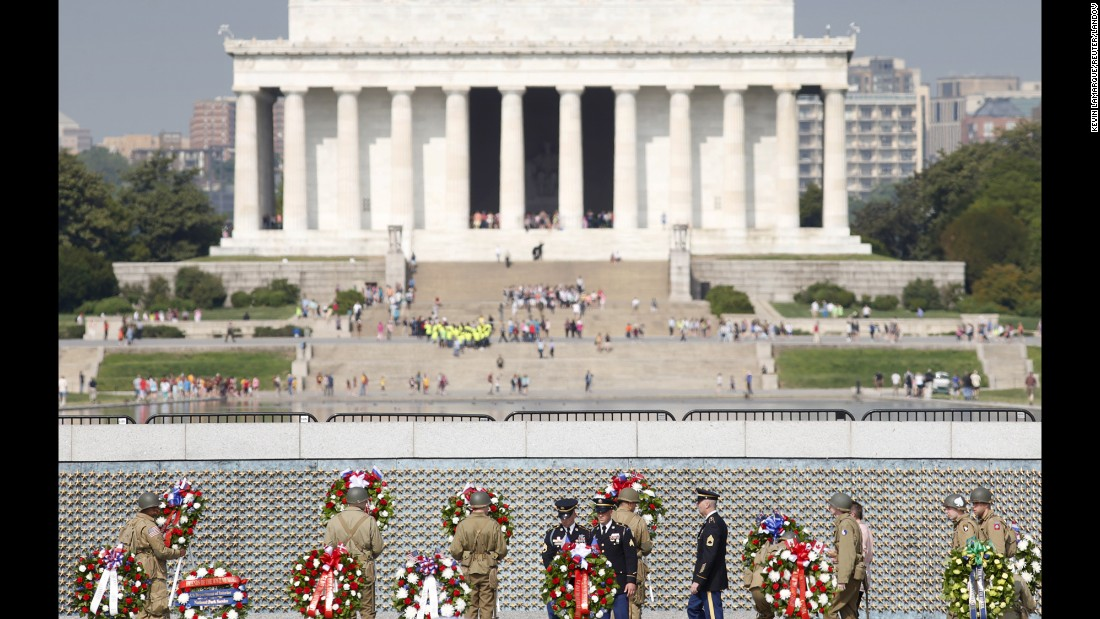 Soldiers dressed in World War II-era uniforms place wreaths in front of the Freedom Wall at the World War II Memorial in Washington.