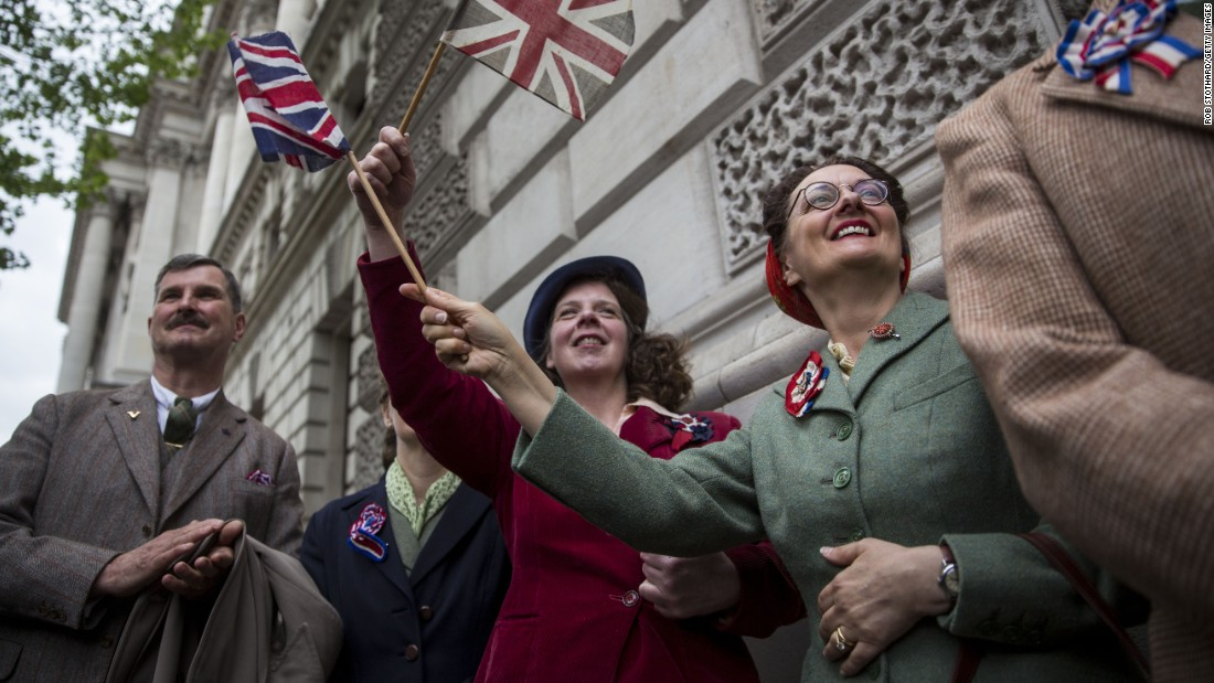 Spectators in London wave flags and wear World War II-era clothing.