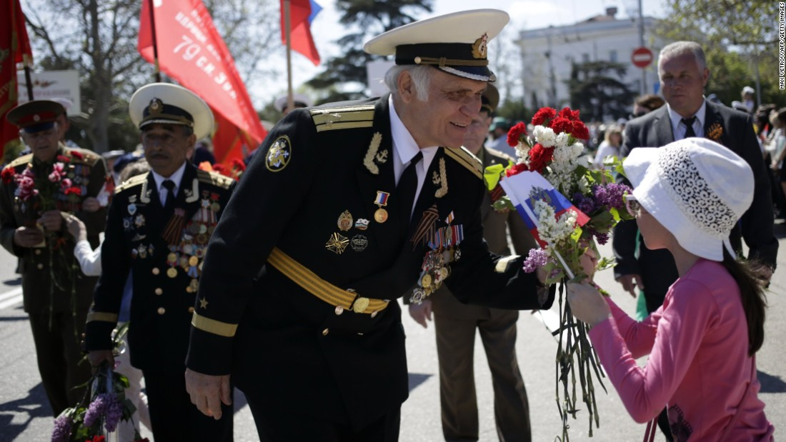 A Crimean veteran accepts flowers from a young girl during a march in central Sevastopol on May 9. Friction continues between Russia and Western nations that were allied with the former Soviet Union during World War II, stemming from Russia's recent actions involving Ukraine, including its annexation of Crimea last year.
