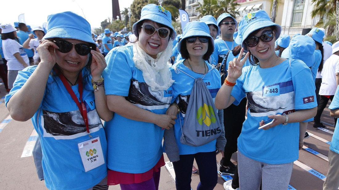 Employees of Tiens group pose for the camera during a parade in Nice, France on May 8.