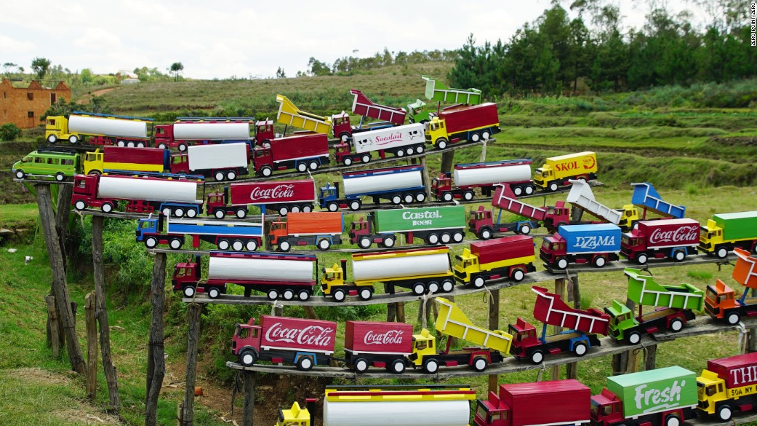 A colorful display of toy trucks is a quirky sight in the green countryside.