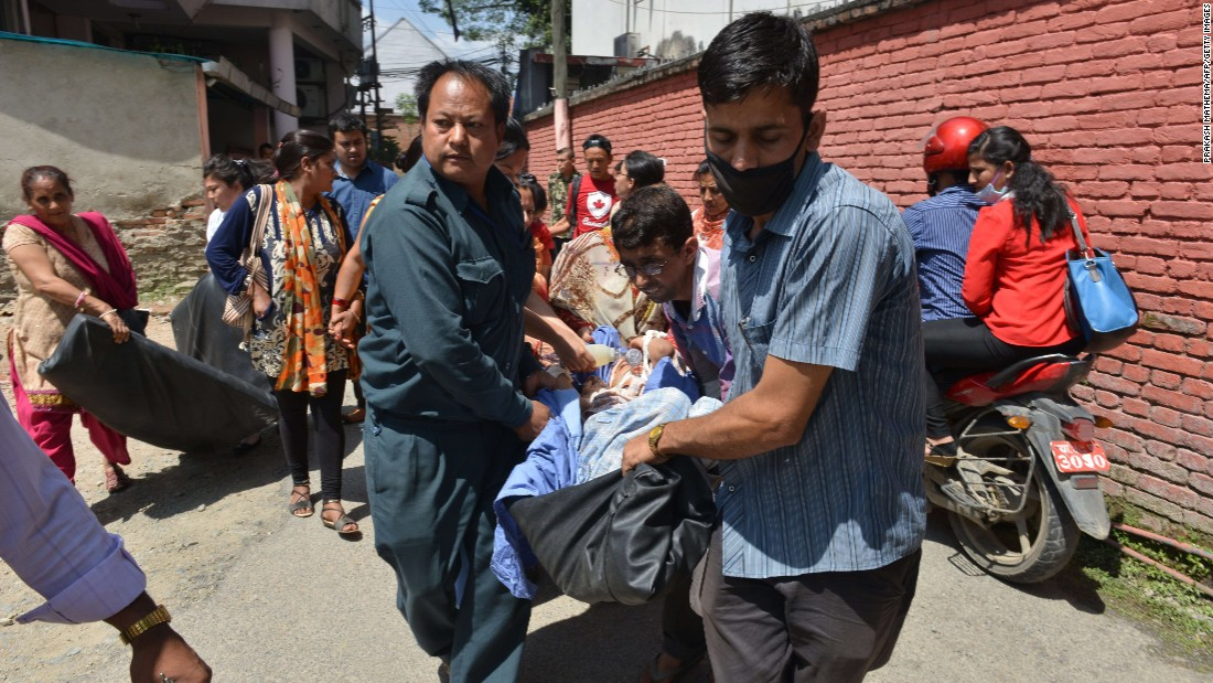 People are carried out of a hospital building in Kathmandu on May 12.